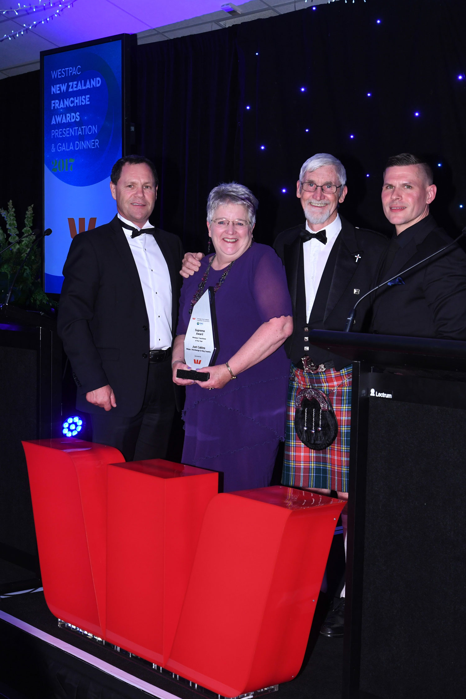 Judi & Earl McWhirter receiving their Supreme Award from Steve Atkinson, Westpac Head of Specialists Commercial (left) and FANZ Chairman Brad Jacobs. Ross is wearing the McWhirter tartan for the occasion.