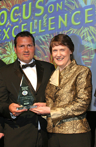 "Stu Beadle of CleanTastic accepts the 2004 Supreme Award from Prime Minister Helen Clark. Both are now US-based."" alt=""Stu Beadle of CleanTastic accepts the 2004 Supreme Award from Prime Minister Helen Clark. Both are now US-based."